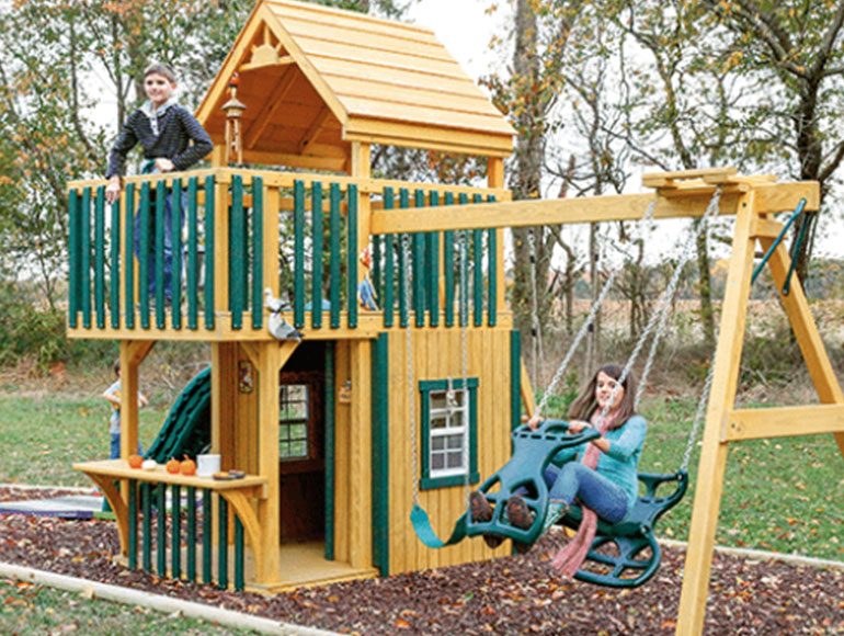 kids playing on wooden swingset with slide